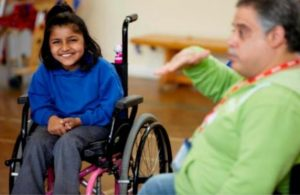 [image: happy girl in wheelchair with carer]